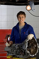 Female mechanic with engine part by elevated car, smiling, portrait