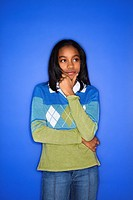 Portrait of African_American girl with hand on chin standing in front of blue background.