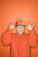 Smiling middle_aged Caucasian man wearing propeller cap on orange background.
