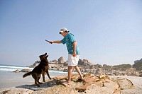 Man on beach, preparing to throw stick for dog, low angle view