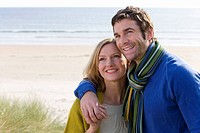 Couple embracing on beach, smiling