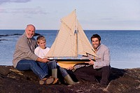 Grandfather, adult son and grandson 7-9 years holding model sailboat by sea, smiling, portrait