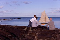 Grandfather, adult son and grandson 7-9 years holding model sailboat by sea, rear view, sunset