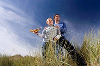 Father standing behind son 7-9 years holding up toy airplane, standing on long grass, low angle view