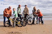 Grandparents with family of four standing with bicycles on beach, smiling, portrait
