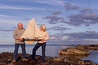 Senior couple with model boat on rocks by sea
