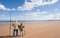 Grandfather and grandson 7-9 on beach with fishing rods, looking out to sea, rear view