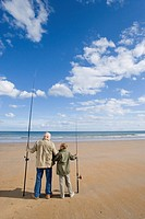 Grandfather and grandson 7-9 on beach with fishing rods, rear view