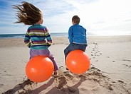 Girl and boy 8-12 playing on inflatable hoppers on beach, rear view