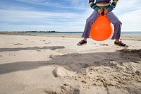 Girl 8-10 playing on inflatable hopper on beach, low section