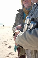 Couple with insulated flasks on beach, mid section