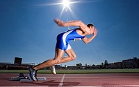 Male sprinter leaving starting block, side view sun flare