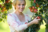 Woman picking apple, smiling, portrait, close-up