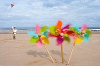 Pinwheels on beach, girl 5-7 flying kite in background blurred motion