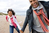 Young couple hand in hand on beach, smiling, portrait