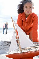 Girl 5-7 with toy boat on beach, smiling, portrait