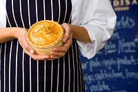 Female baker with pie, mid section