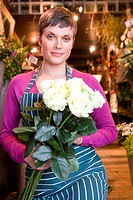 Female florist with bunch of roses, smiling, portrait
