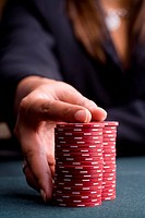 Woman with hand on pile of gambling chips, close-up of hand