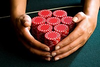 Woman with hands around piles of gambling chips on table, close-up