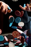 Woman dropping gambling chips on table, close-up of chips falling