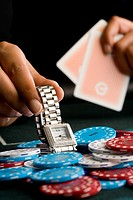 Woman placing watch on pile of gambling chips on table, close-up (thumbnail)