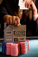 Woman placing model house on pile of gambling chips on table, mid section