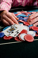 Man collecting pile of gambling chips on table, close-up of winning cards (thumbnail)