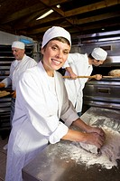 Female baker kneading dough, smiling, portrait