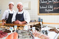 Fishmongers behind counter in shop, smiling, portrait (thumbnail)