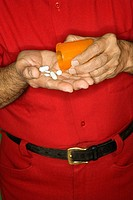Mature adult Caucasian male emptying pill bottle into hand.