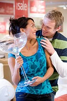 Young woman with giant cocktail glass in shop, smiling at man