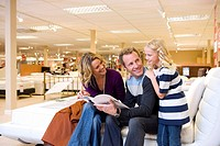Family of three in furniture shop, parents smiling at daughter 6-8