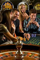 Men and women gambling at roulette table, smiling