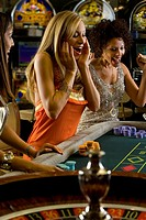Young women gambling at roulette table, smiling in celebration
