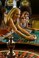 Young woman collecting pile of gambling chips at roulette table, smiling