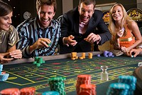 Men and women gambling at roulette table in casino, smiling