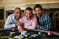 Young man flanked by friends gambling at poker table in casino, smiling, portrait