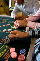 Young men gambling at poker table in casino, section (thumbnail)