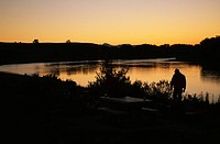 Campers at sunset by the Missouri River.