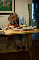 A mother eats her breakfast with her four_year_old son.