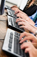 Close up of executives typing on keyboards.