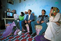 The whole family is watching an interesting TV show .City of Cairo. Egypt.