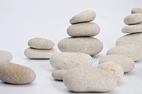 Stacks of smooth pebble stones, white background