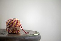 Ball of multi_coloured wool on wooden stool