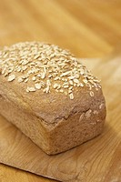 Bread with oat on wooden cutting board