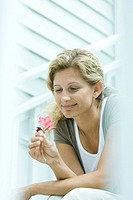 Woman looking down at flower in hand, smiling