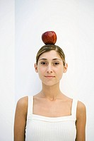 Woman balancing apple on her head, smiling at camera, portrait