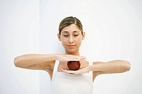 Woman balancing apple between hands, eyes closed
