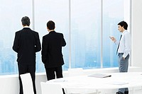 Businessmen standing by window in conference room, one checking cell phone